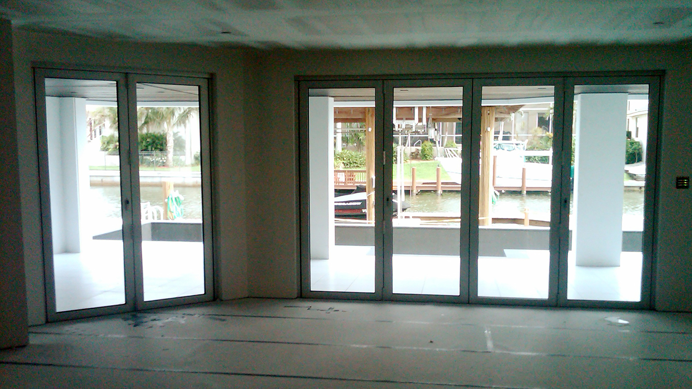 Thirteen sets of folding glass walls used on a residential home. Units consist of all wall and single door last panel configurations, along with recessed sill and impact glazing.