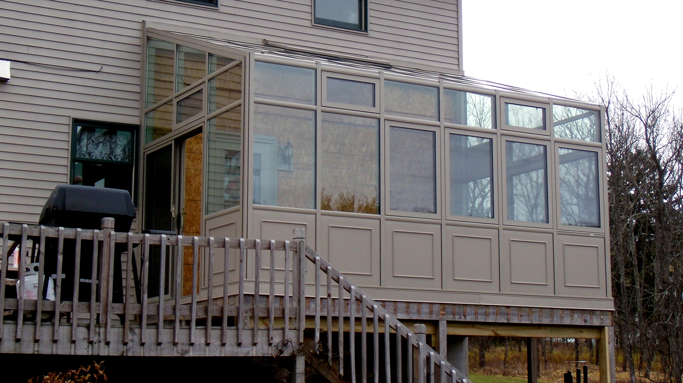 Straight eave lean to sunroom with two gable ends, a sliding door system, operable windows and raised base panels.