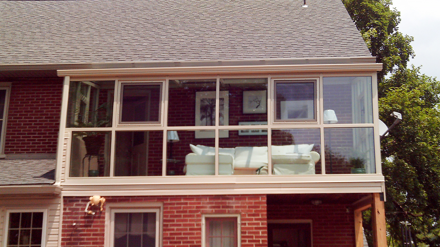 Straight eave lean-to sunroom with two gable ends, located on a second story application, with tilt turn windows and a ridge vent.