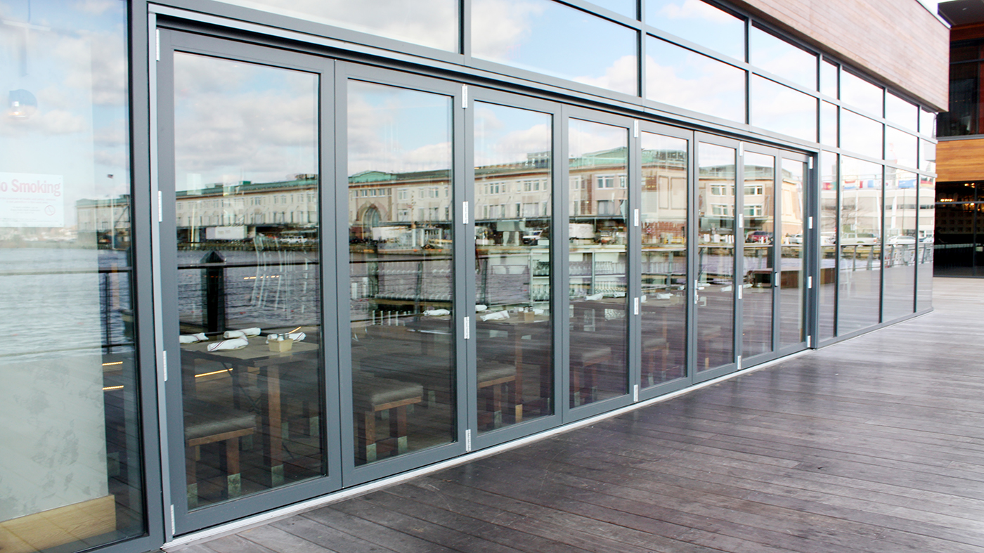 Three Double Door Mid Wall Folding Glass Wall Units installed at Boston's Liberty Wharf. 5 panels fold left, 3 panels fold right, recessed sill with interior and exterior ramp.