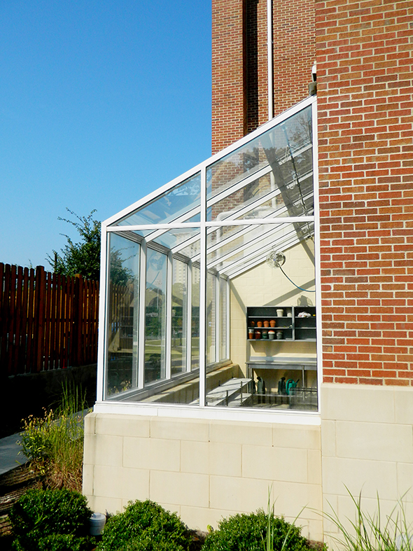 Straight eave, lean-to greenhouse with one gable end and ridge vents.