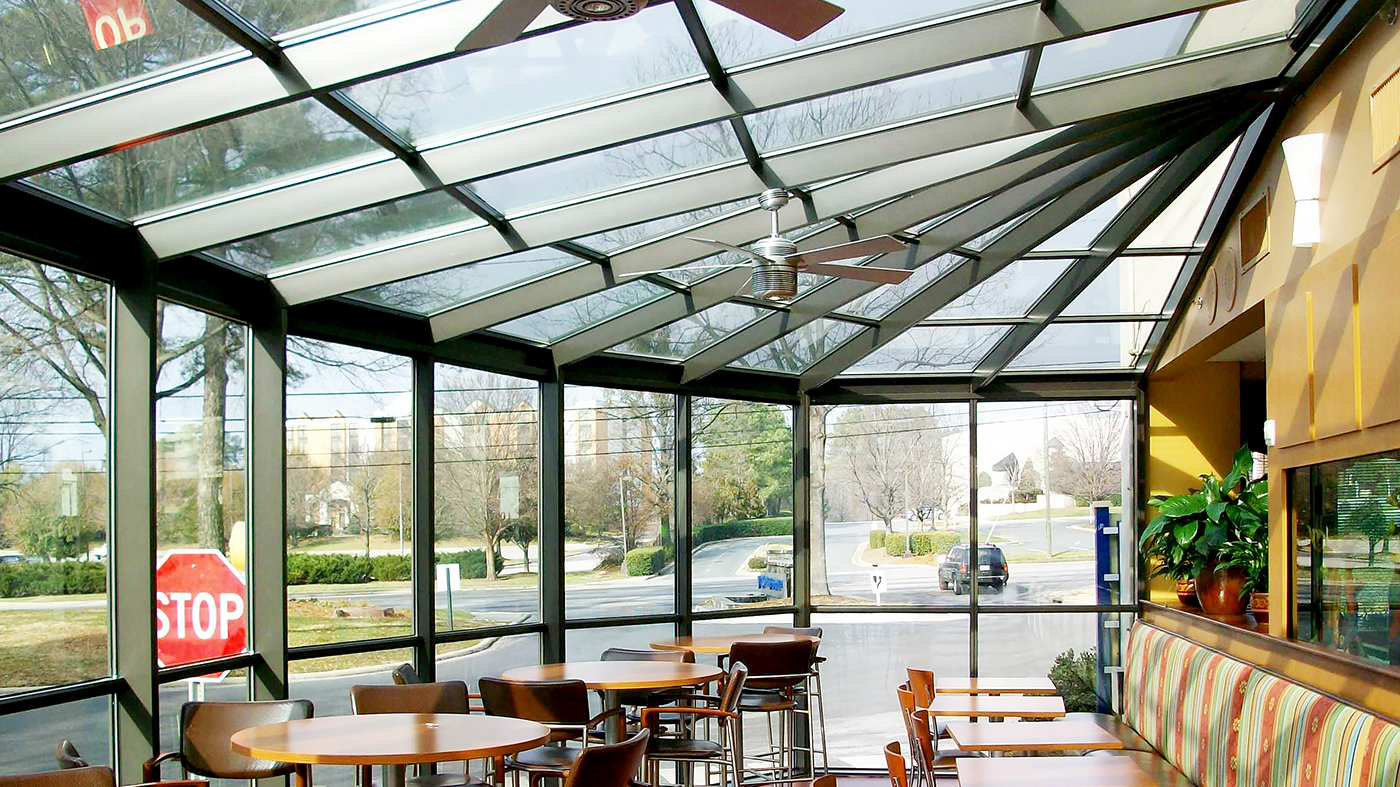 Straight eave lean-to sunroom with irregular conservatory quarter nose.