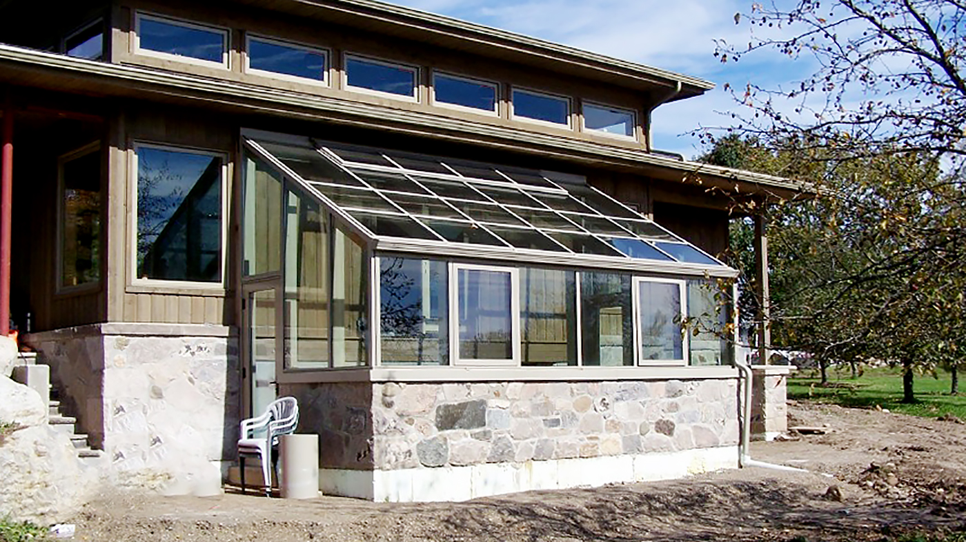 Straight eave lean-to greenhouse with two gable ends including decorative gutters, ridge vents, awning windows and a terrace door.