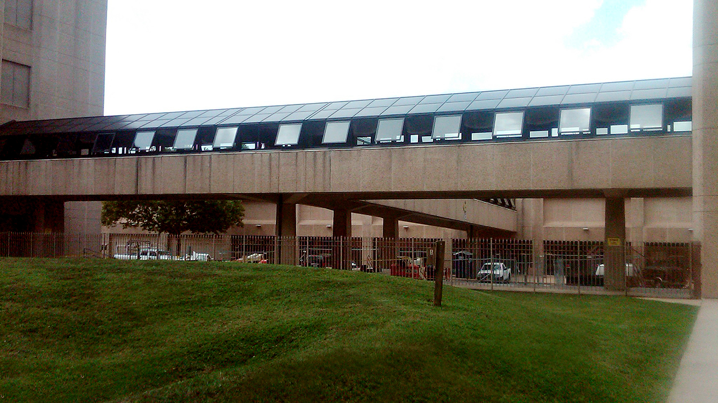Commercial, sloped, covered walkway. T-Shape to create connection between three buildings.