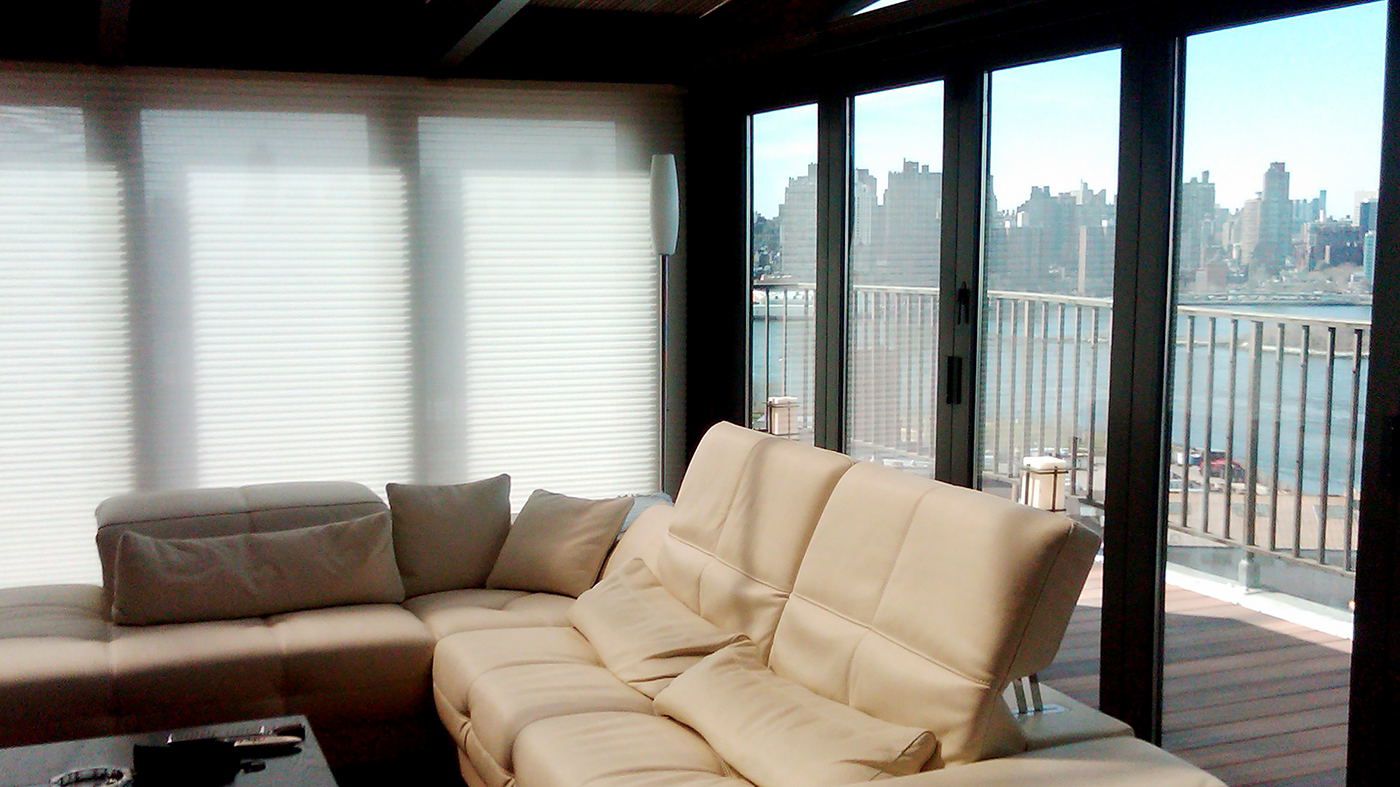 Straight eave lean-to sunroom with one gable end, located on a highrise in an urban setting. Unit includes folding glass walls and a polycarbonate roof.
