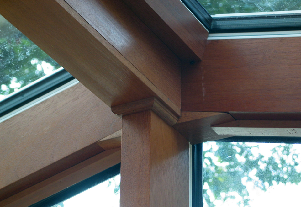Straight eave double pitch sunroom with one gable end, aluminum exterior with a mahogany wood interior, ridge vents, windows and terrace door.