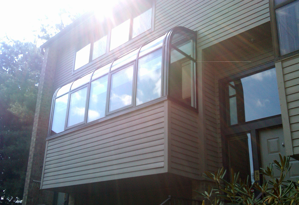 Curved eave lean-to greenhouse attached to a residential home.