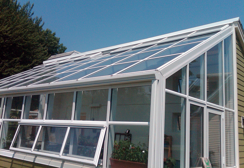Irregular straight eave lean to greenhouse with operable eave sashes and ridge vents, terrace door, gutter and downspout.