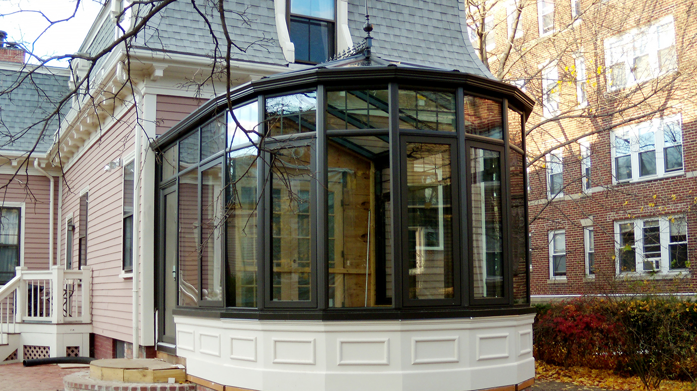 Transoms create a geometric pattern around the top of the 8-panel nose of this conservatory. Other decorative elements include ridge vents, ridge cresting, finials, and interior muntins.