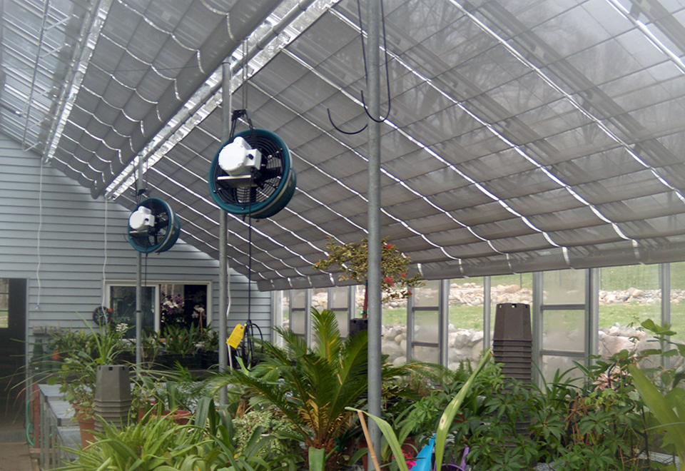 Existing greenhouse with retrofits by Solar Innovations. Additions include an operable, roof mounted shade system, humidifiers, ridge vent replacement, and fixed mesh top benches.