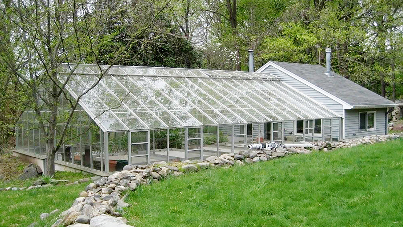 Existing greenhouse with retrofits by Solar Innovations. Additions include an operable, roof mounted shade system, humidifiers, ridge vent replacement, and fixed mesh top benches.P