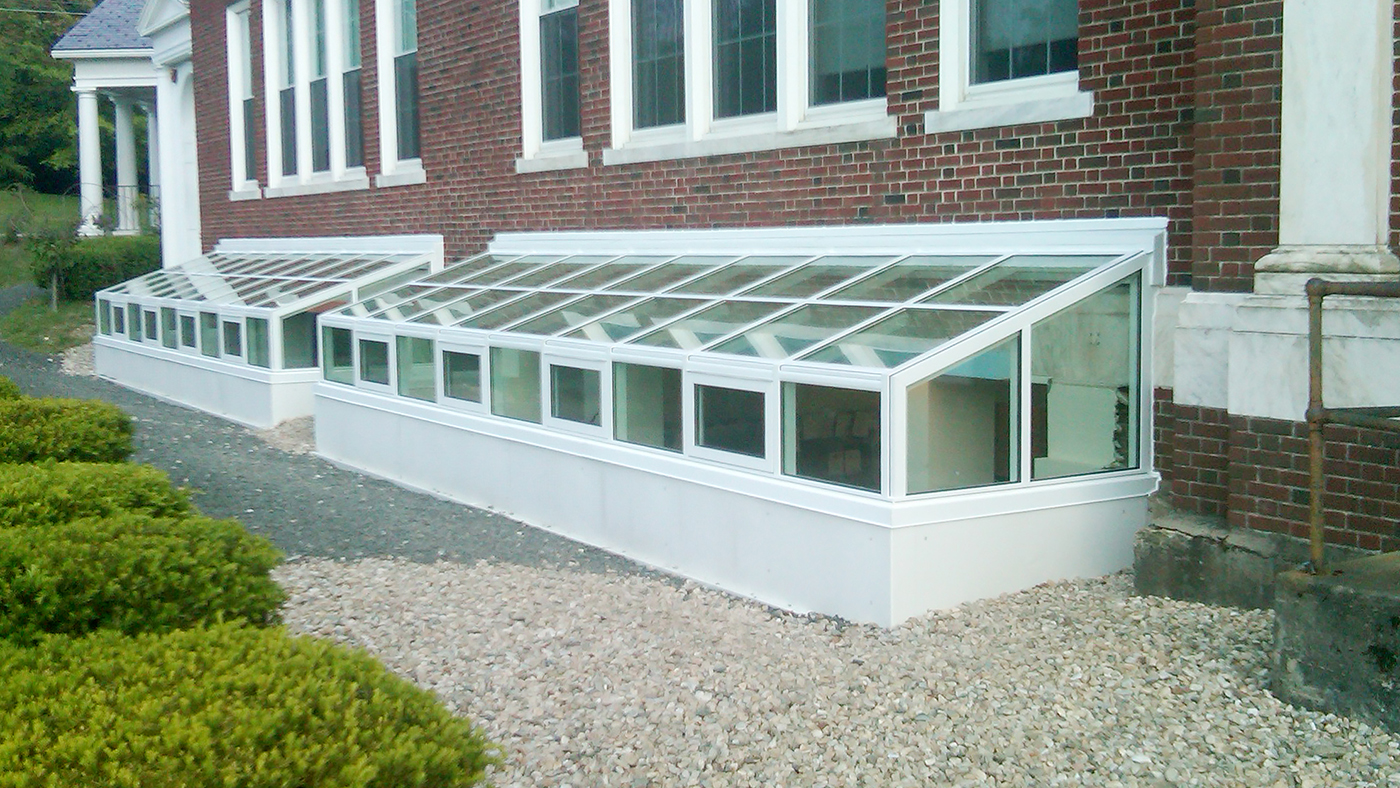 Two straight eave lean-to window well covers with gable ends.