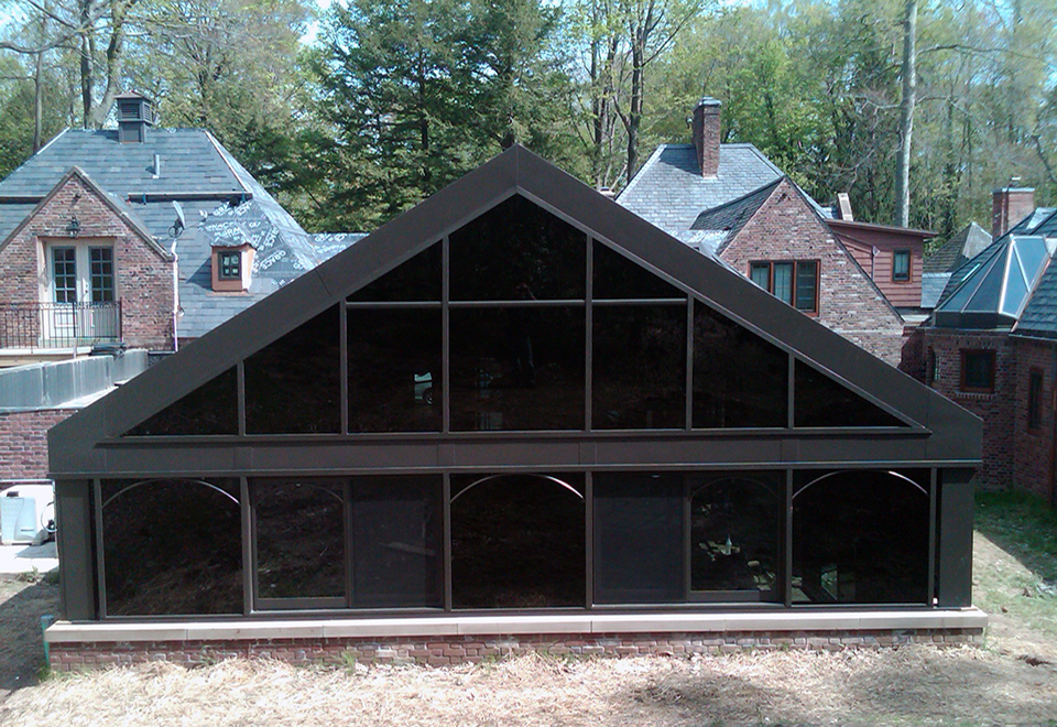 Irregular pool enclosure featuring a conservatory nose and dormers with specialty graylite 14 over 366 glazing. Traditional construction roof engineered by Solar Innovations. Windows feature a decorative radius grid.
