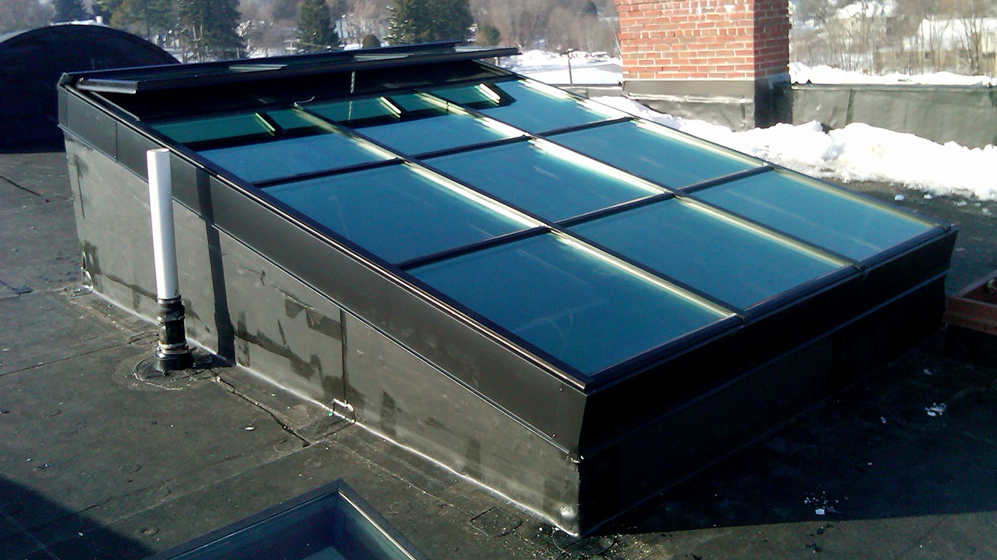 Curb mounted flat skylight with operable ridge vents