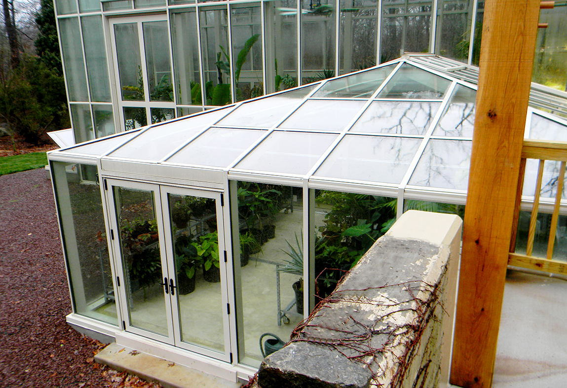 Straight eave double pitch greenhouse with 2 partial side walls, interior partition wall, and straight eave double pitch structure with hip end, connected to sidewall of main greenhouse. Cold frames are located on the exterior of the greenhouse. Interior growing accessories include ridge vents, eave vents, circulation fans, grow lights, and misting system.