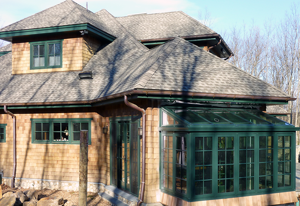 Straight eave lean-to sunroom with two gable ends, casement windows, and decorative elements including transom, gutter, and downspout.