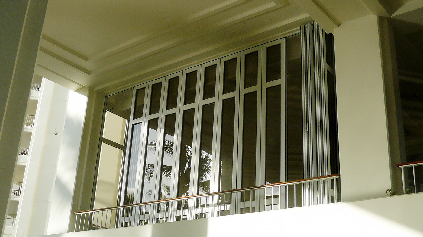 Multiple folding glass wall units used on a hotel including a center pivot folding wall with a split wall configuration and surface mount sill, sliding door and curtain wall, all with monolithic glazing.