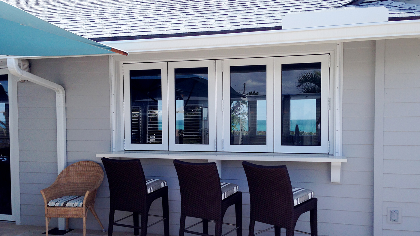 Multiple sets of folding glass walls, using recessed sills with adjustable ramps, located on a private beach club.