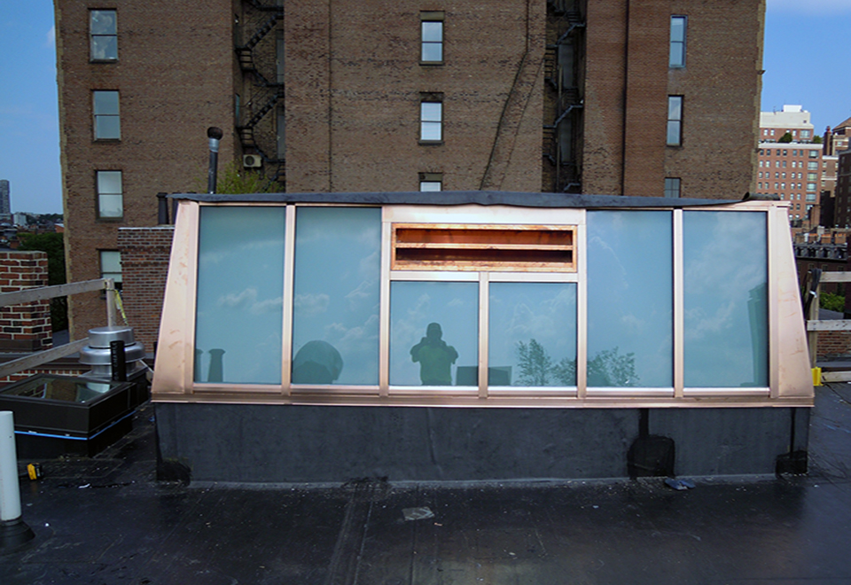 Lean-to skylight enclosing elevator shaft featuring Copper cladding exterior and white laminated glazing.