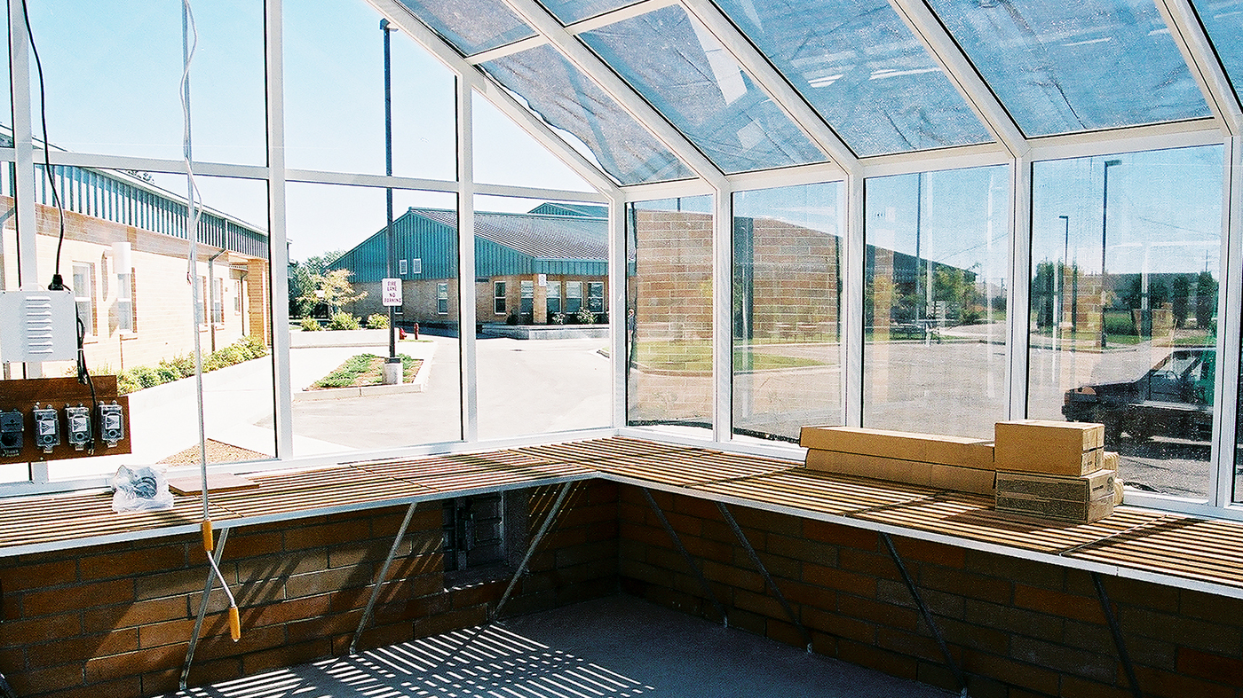 Straight eave, double pitch greenhouse with operable ridge vent and in-system terrace door.