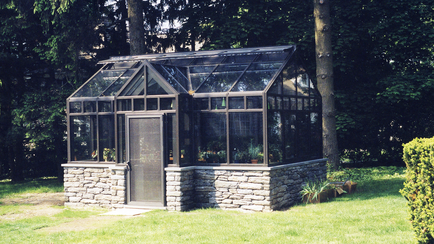 Straight eave double pitch greenhouse with projected dormer, projected windows, ridge vents, and terrace door.