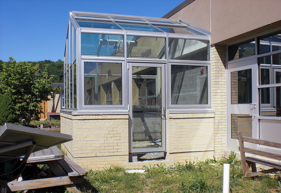 Straight eave double pitch educational greenhouse with ridge vents, awning windows, terrace door, temperature control system, and circulation fan.