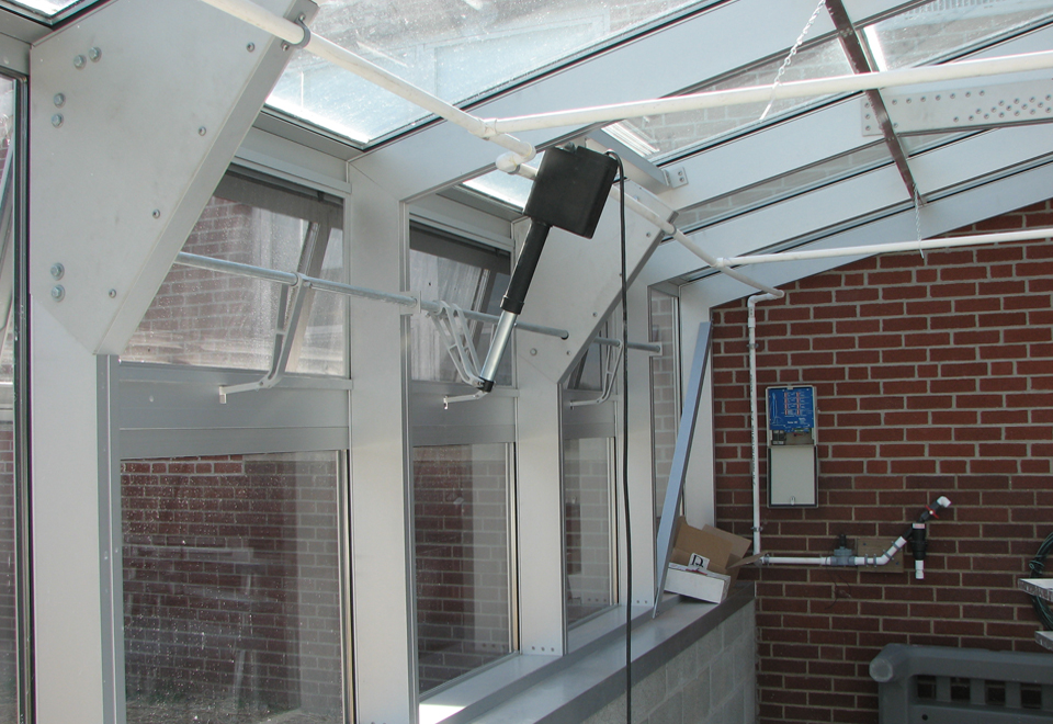 Straight eave, double pitch greenhouse with operable ridge and eave vents.