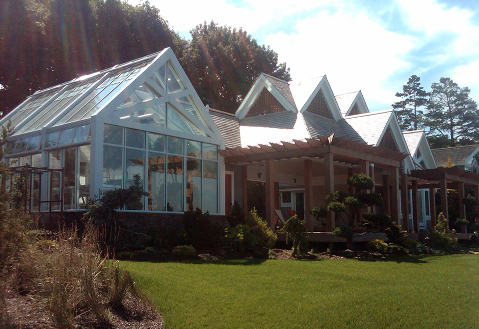 Straight eave double pitch greenhouse with two gable ends, true divided pediment, two interior trusses, benches and operable shade system.