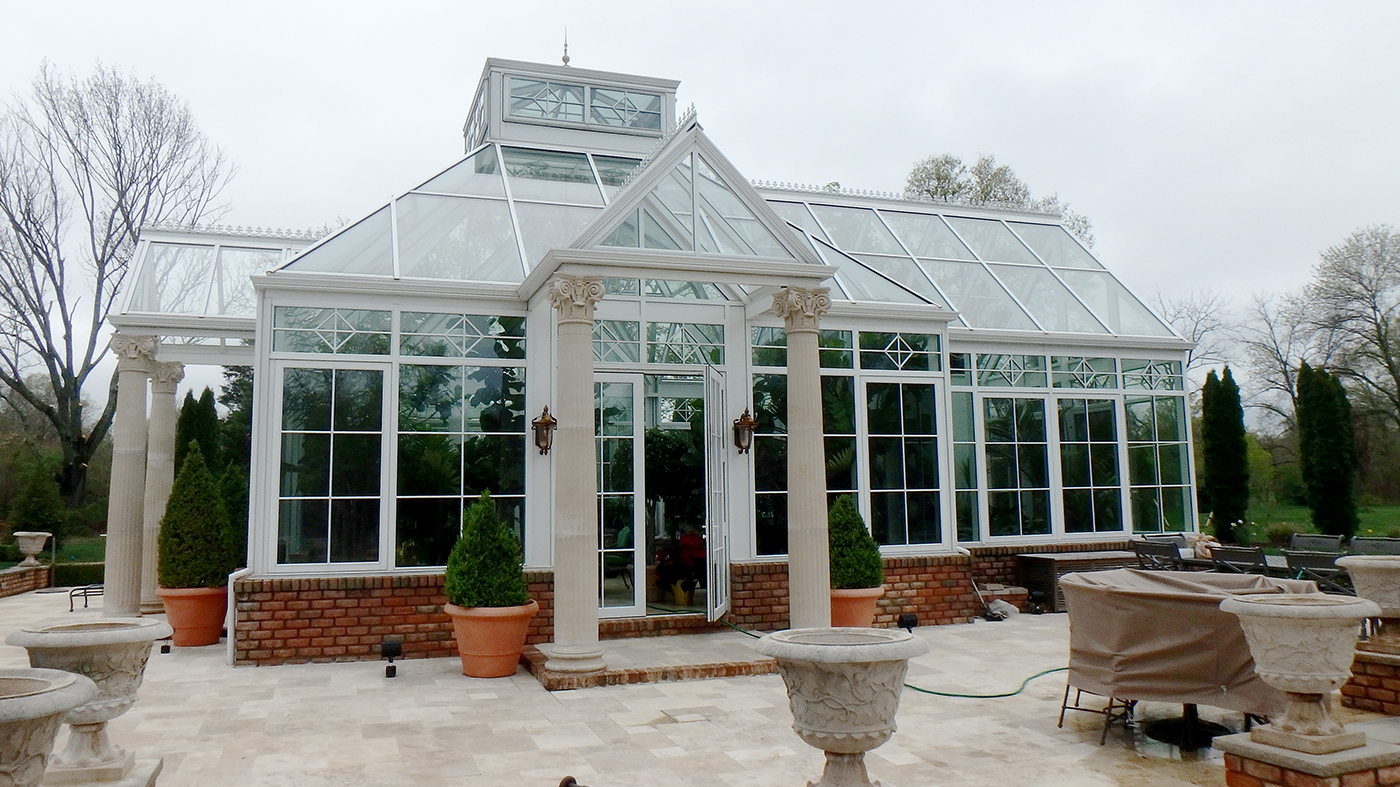 Straight eave pyramid conservatory with four double pitch lanterns, two interior partitions, transoms, gridwork, gable rake molding, gutter, downspout and a pyramid lantern.