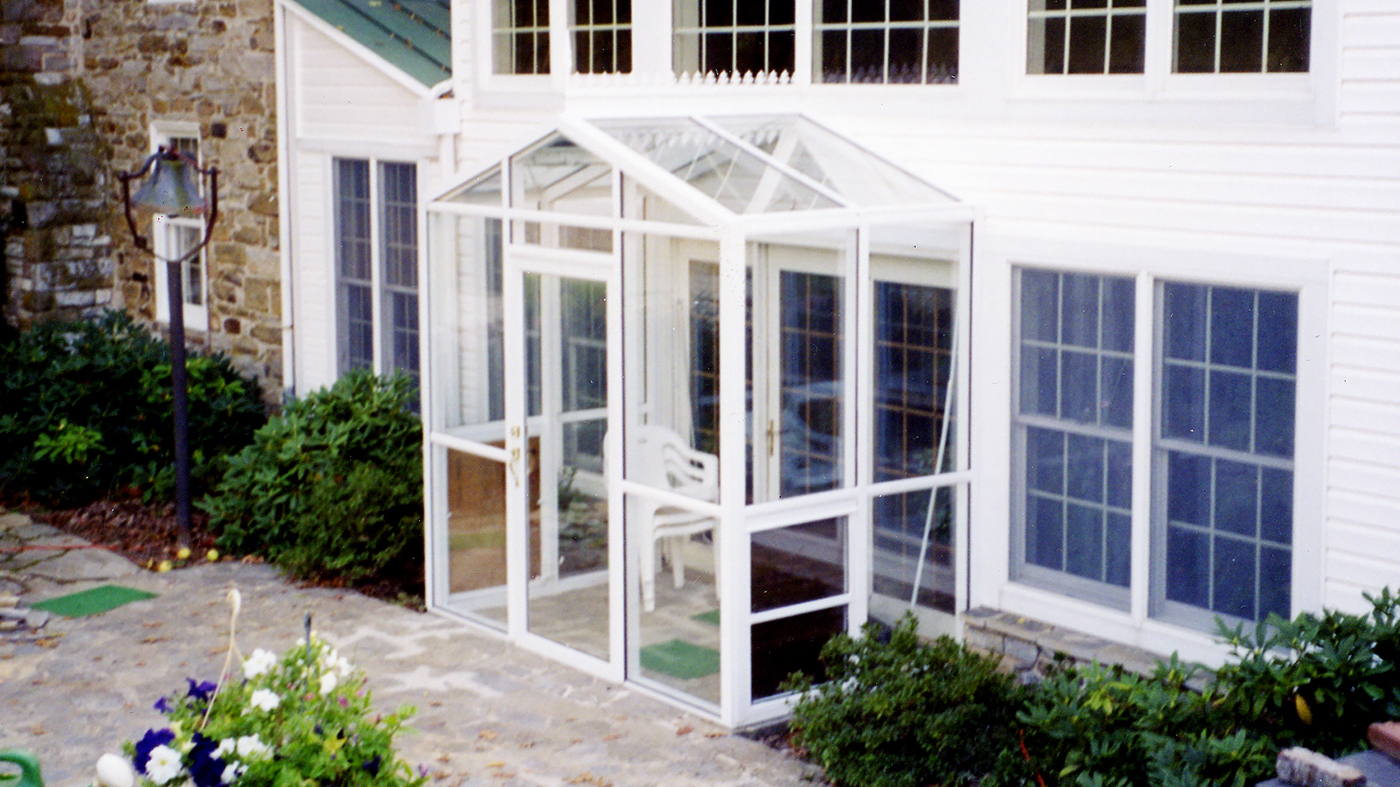 Straight Eave double pitch sunroom with one gable end. Features a terrace door, awning windows, a finial, and ridge cresting
