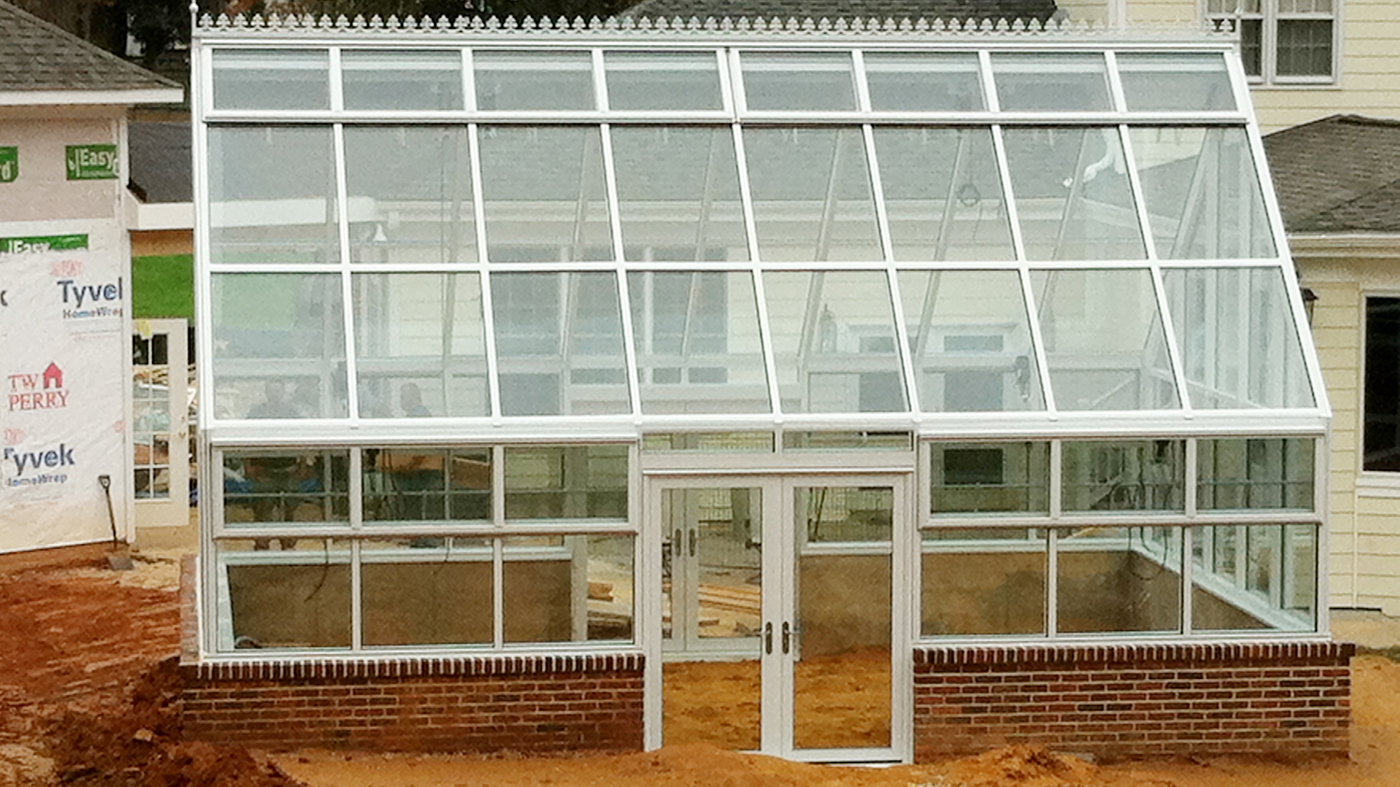 Straight eave double pitch greenhouse with two gable ends, ridge vents, eave vents, finial, ridge cresting, and French doors