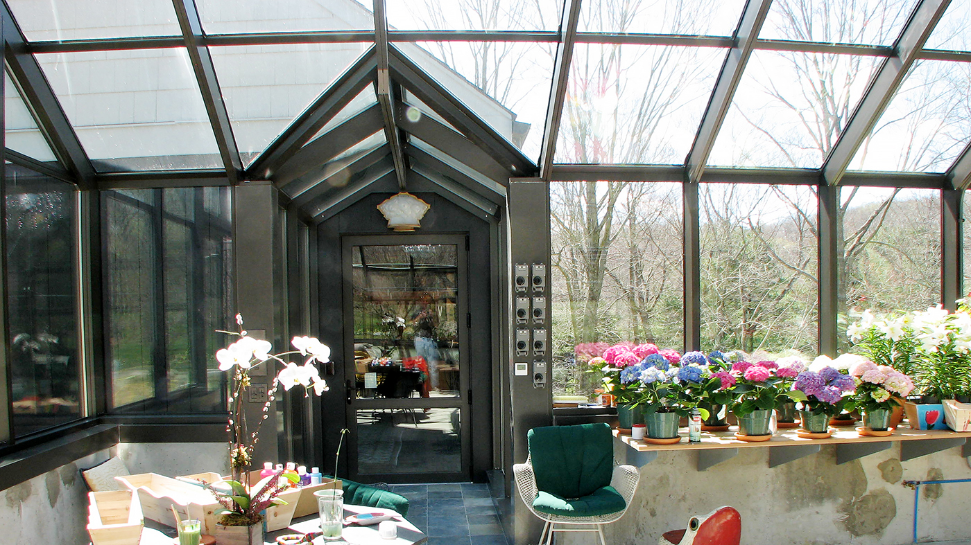 Straight eave double pitch greenhouse with two gable ends, attached double pitch walkway, French doors, ridge vents and eave vents, and decorative elements.