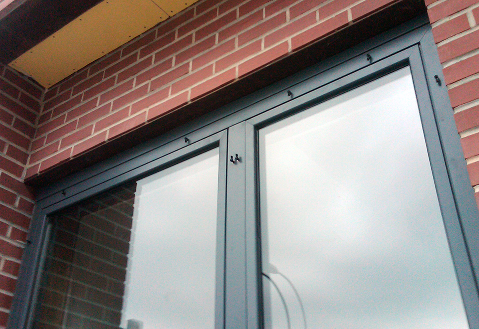 Double tilt turn window with fixed astragal using the European window system and a three-panel folding glass wall system with obscure #62 acid etch glass.