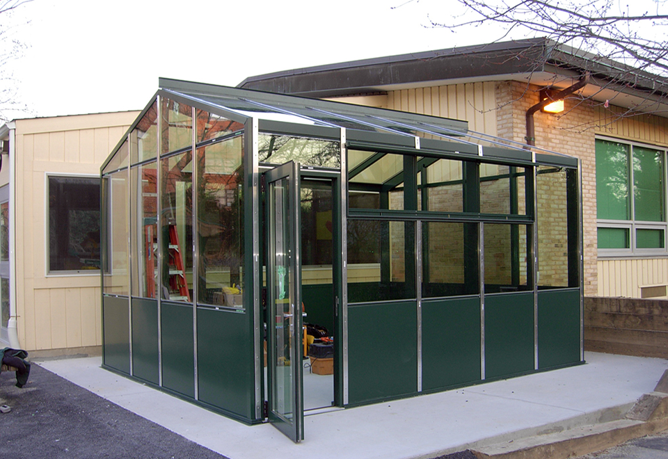 Straight eave double pitch greenhouse with two gable ends including circulating fans, eave vents, base panels and a terrace door.