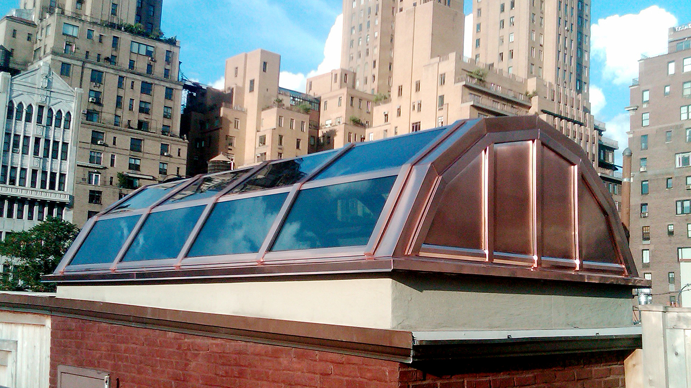 Segmented radius exterior skylight with two gable ends featuring White Oak LVL interior rafters and wood sill and Copper metal cladding exterior.