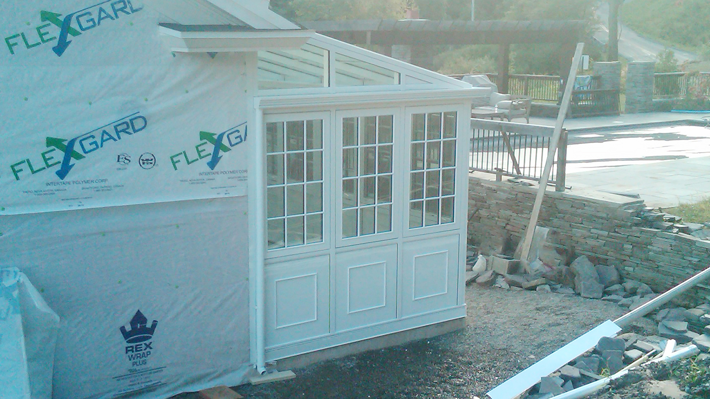 Straight eave lean-to conservatory with one gable end, raised interior and exterior base panels, SDL's, ridge vent, gutter, interior Ogee capping, bull nose trim and casement windows.