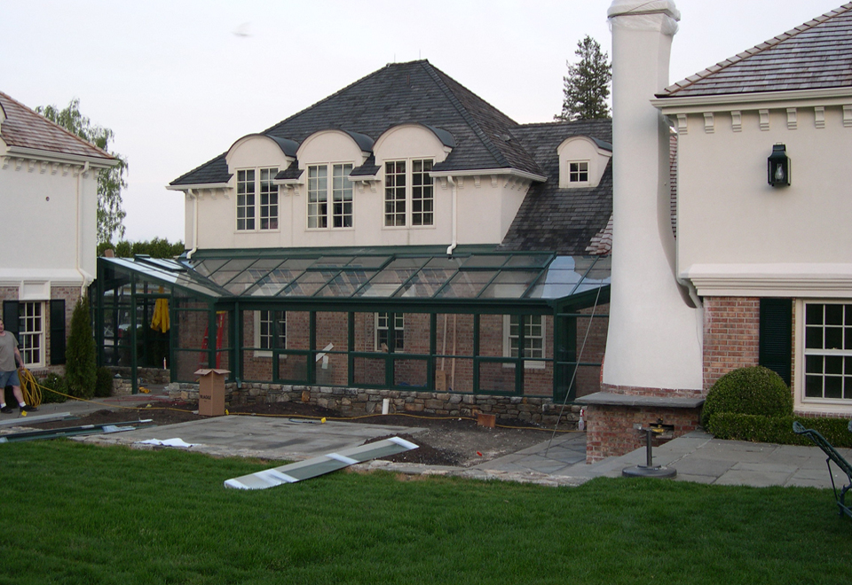 Straight eave lean to enclosure with a 90 corner on 1 side and attaching to a hip valley structure with 2 partial gable ends.