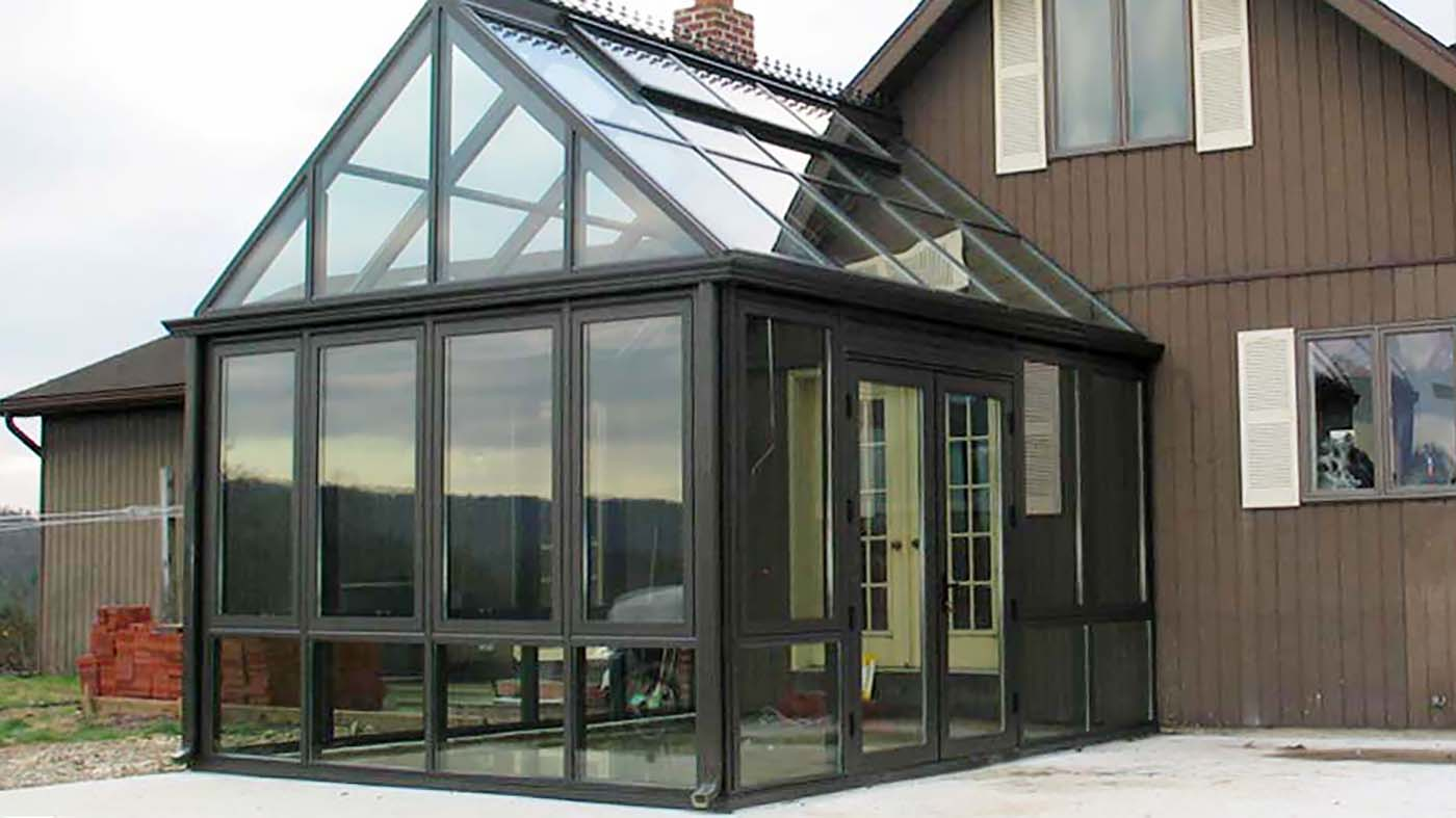 Straight eave, double pitch greenhouse with ridge vents, French doors, and decorative elements including ridge cresting and finial.