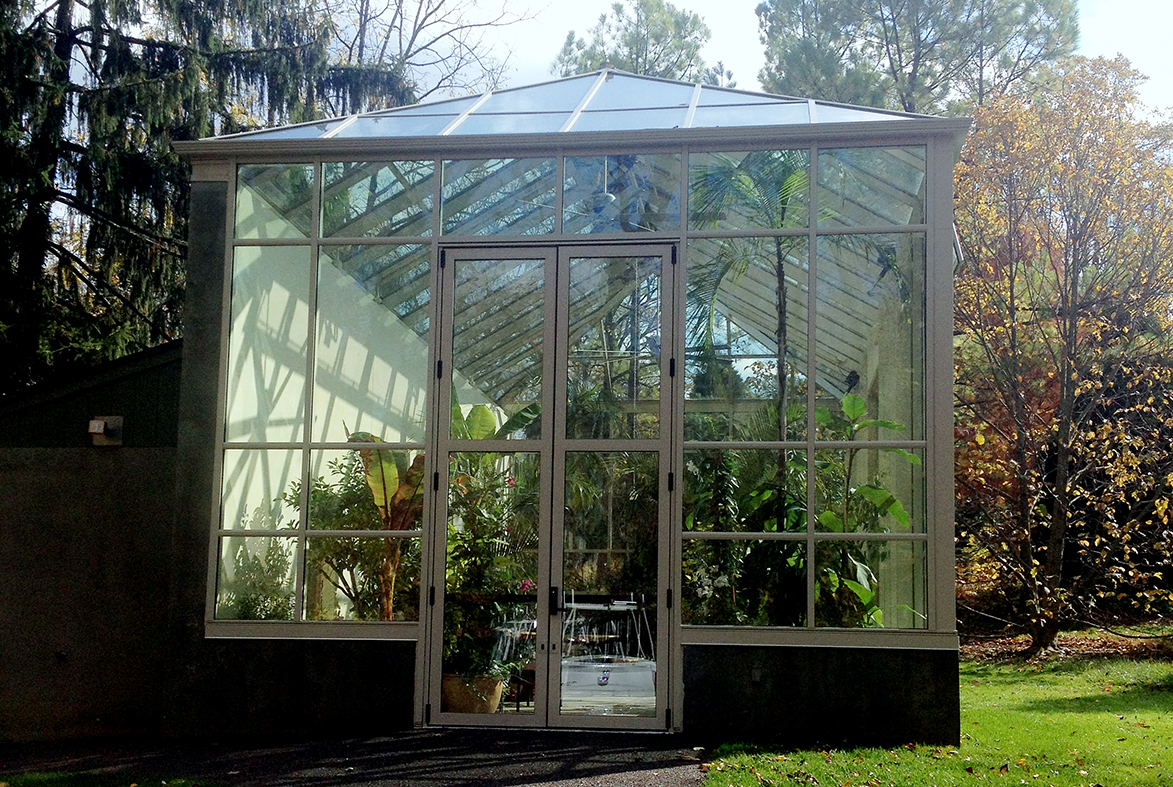 Two sets of massive French doors complement this tall standalone greenhouse.