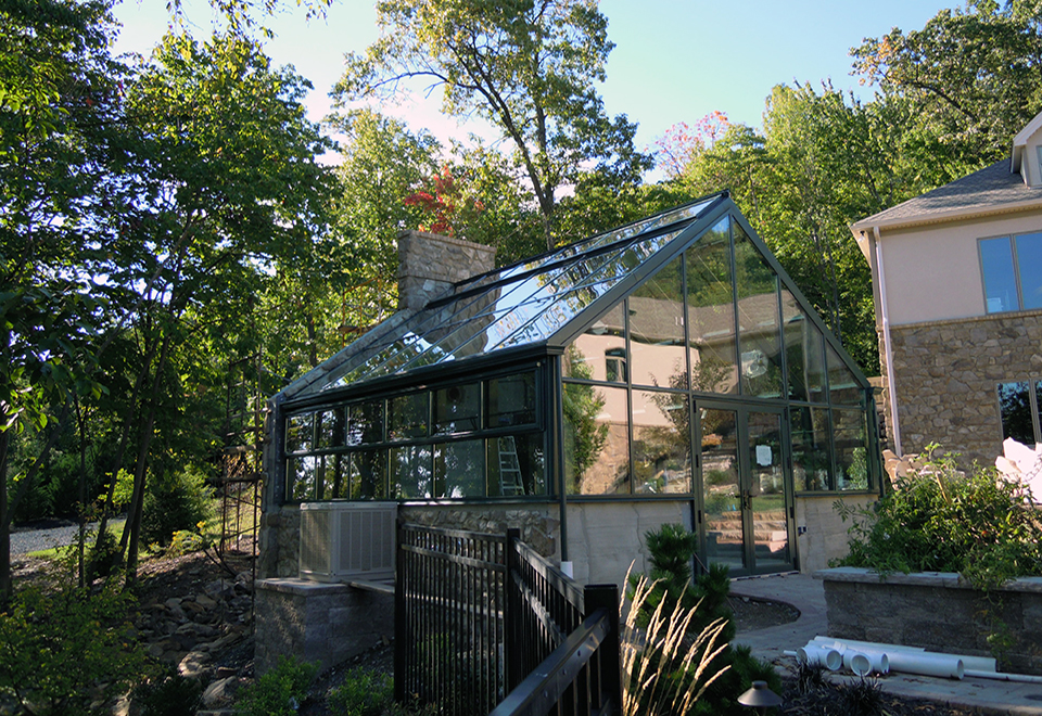 Straight eave double pitch greenhouse with 1 gable end, eave and ridge vents, circulation fans, heater, evaporative cooler and a ring and collar tie bar.
