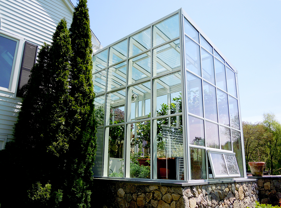 Straight eave lean to greenhouse with two gable ends, ridge vents, eave vents, terrace door, sliding door, heater, circulation fan and aluminum tube plant hanger.
