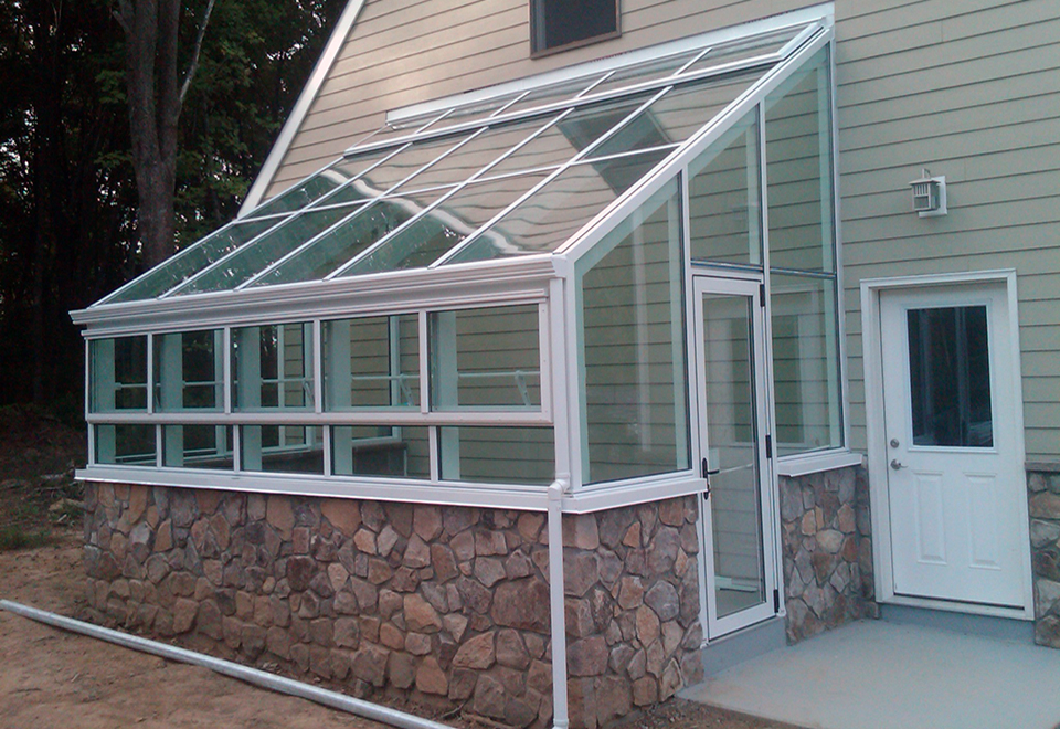 Straight eave lean-to greenhouse with ridge vents and eave vents along with a gutter and downspout. Interior greenhouse accessories include a heater and circulation fan.