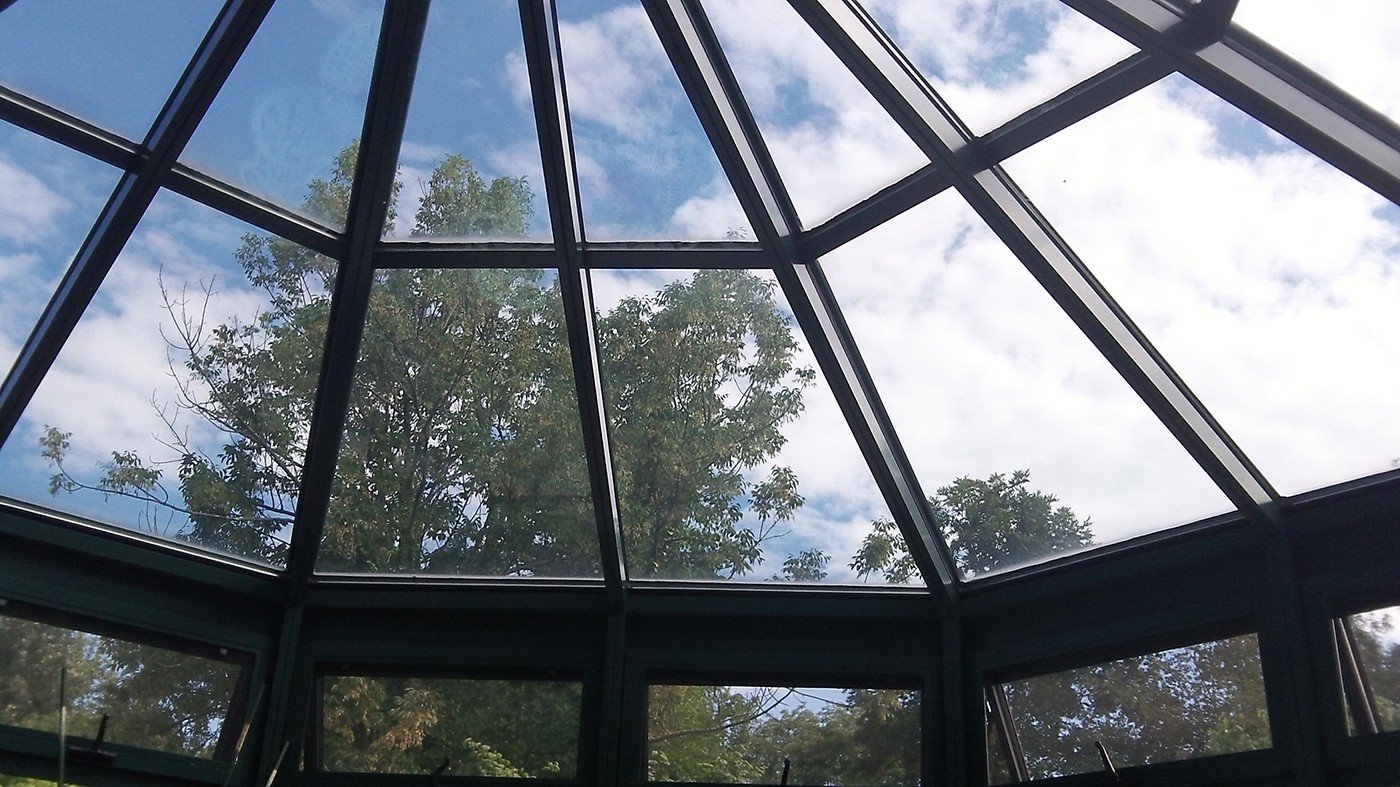 A straight eave double pitch conservatory with one conservatory nose, awning windows, ridge vents, finial, ridge cresting, gutter and downspout.