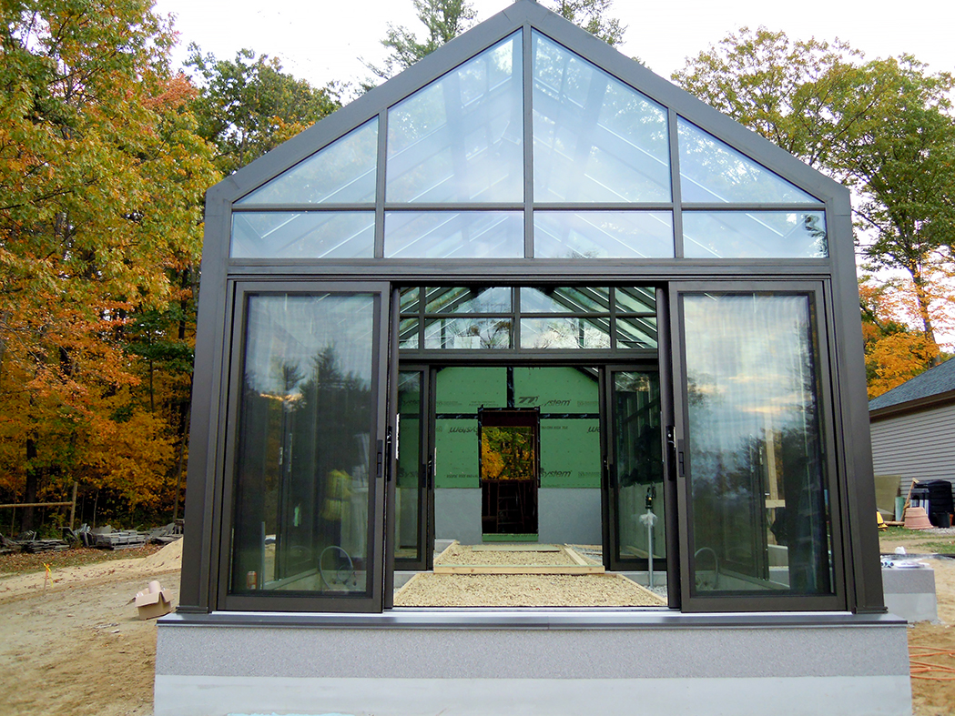 Straight eave lean-to greenhouse with one gable end and one interior wall. Unit features ridge vents, eave vents, sliding doors and an interior ring and collar.