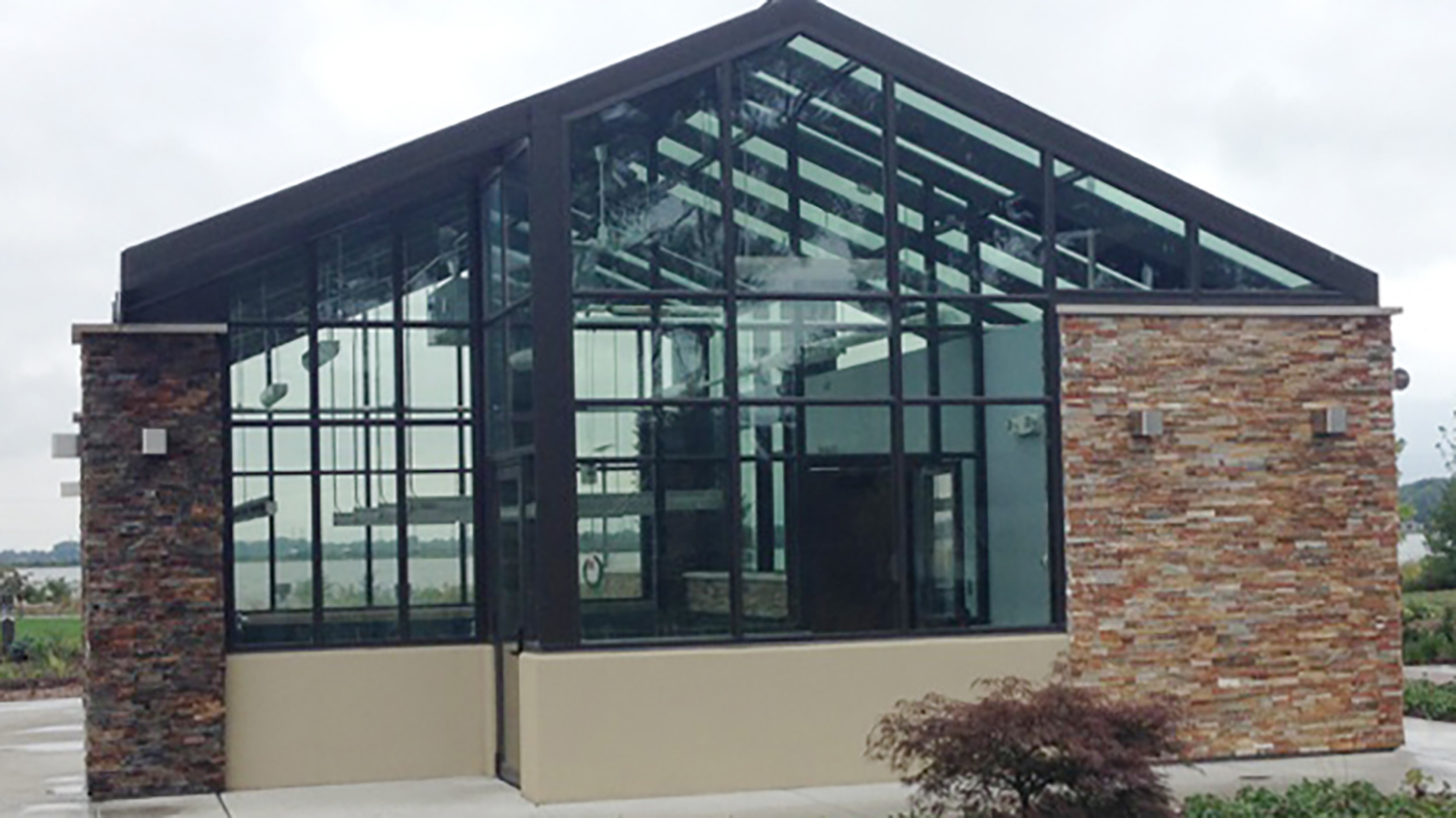 Irregular straight eave double pitch greenhouse with two gable ends, a cantilevered canopy, ridge vents, and eave vents used at a public park.