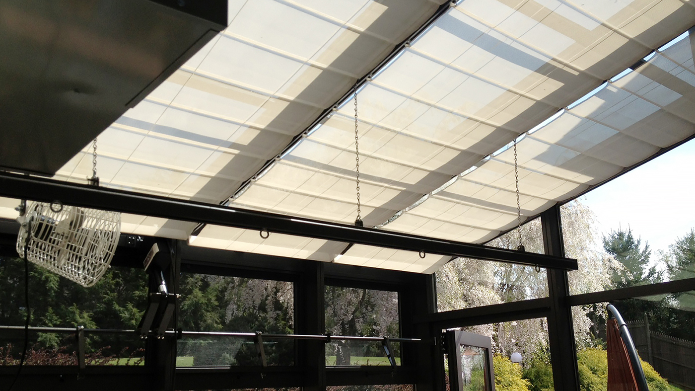 Straight eave lean-to greenhouse with interior roof mounted shades.