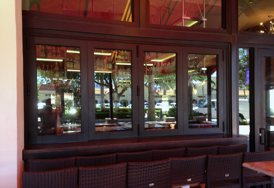 Multiple sets of folding glass windows and folding glass walls used at a restaurant with impact glazing. Each unit has an all wall configuration, folds out, and uses varying sills.