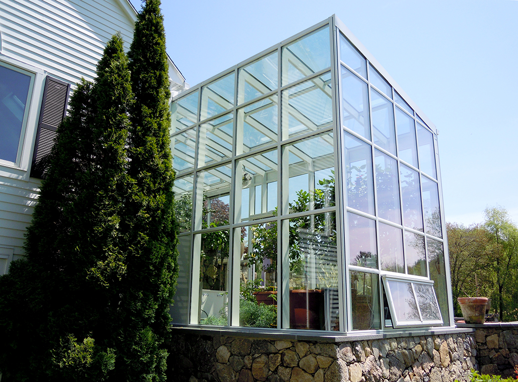 Straight eave lean-to greenhouse with a rear wall. This was an addition to an existing Solar Innovations greenhouse built the previous year.