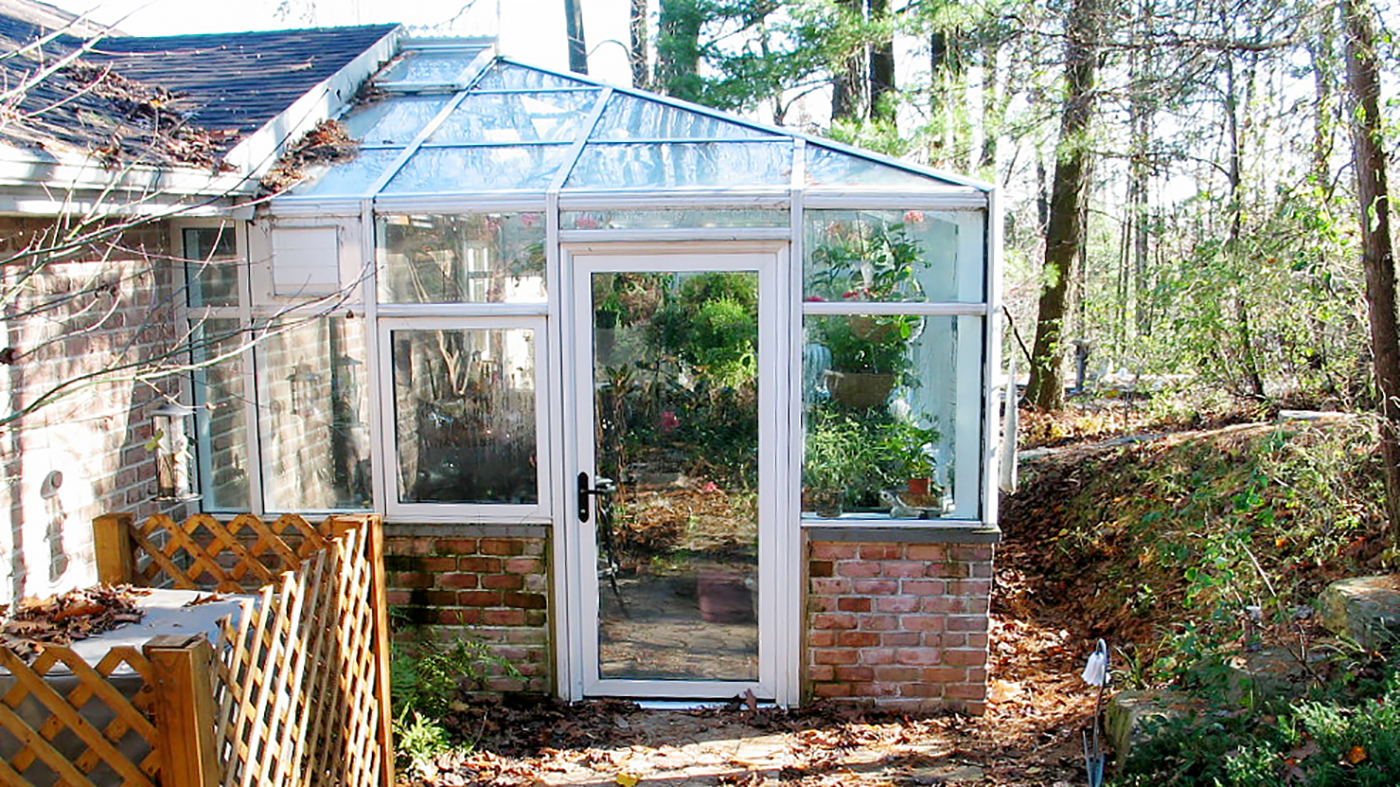 Straight eave, double pitch greenhouse with one hip end, awning windows, terrace door, ridge vents, finial, and ridge cresting.