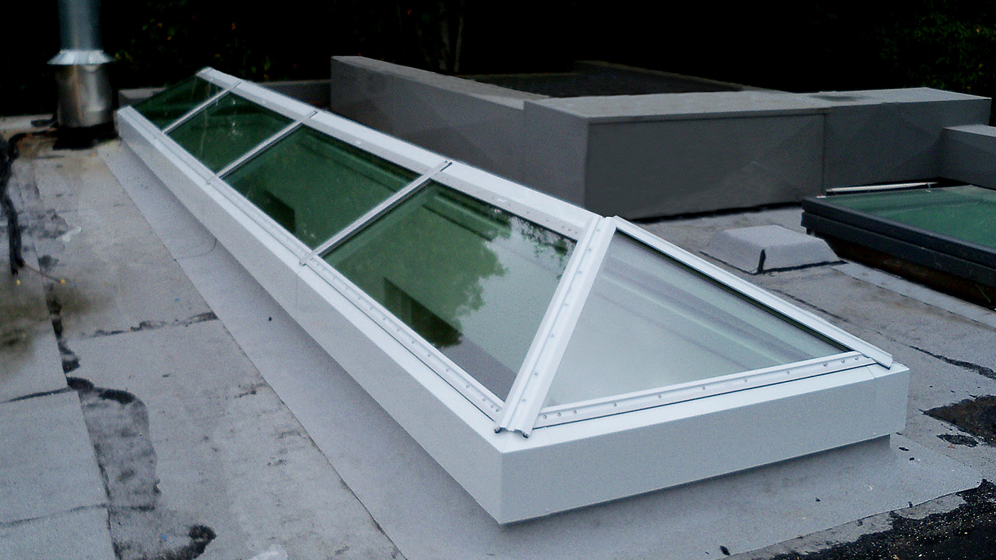 Curb mount hip end double pitch skylight